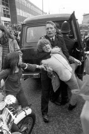 boy-is-held-around-the-neck-by-a-helmetless-policeman-during-scuffles-picture-id834798772